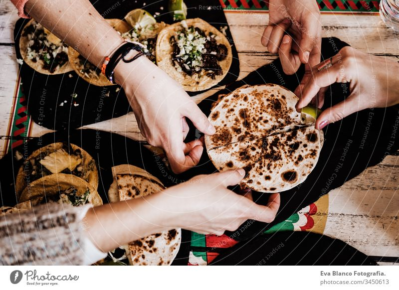 unrecognizable group of friends eating mexican food in a restaurant. Delicious fajitas. Lifestyle outdoors tacos evening celebration female couple drink indoor