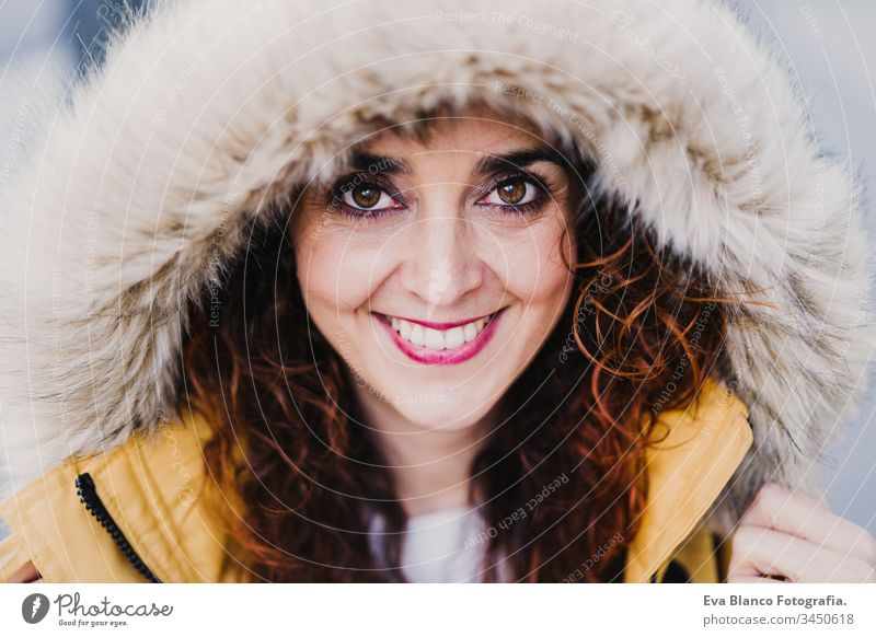 portrait of young beautiful woman wearing a hood smiling outdoors. Happiness and lifestyle yellow coat happiness city urban street smile happy caucasian adult
