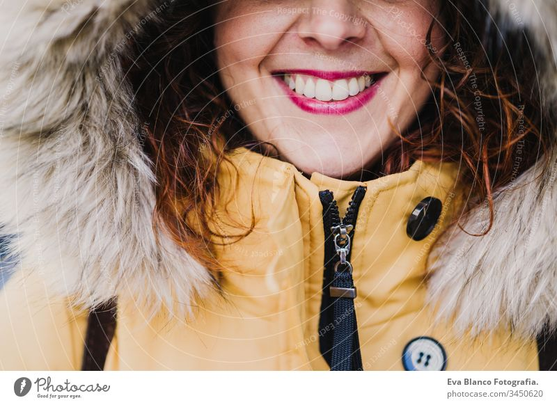 portrait of young beautiful woman wearing a hood smiling outdoors. Happiness and lifestyle unrecognizable yellow coat happiness city urban street smile happy