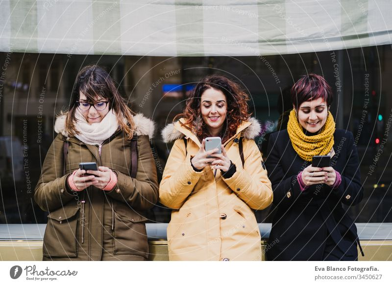 group of friends using mobile phone outdoors in the street. Happy women smiling. lifestyle and travel concept friendship tourist tourism three 3 technology city