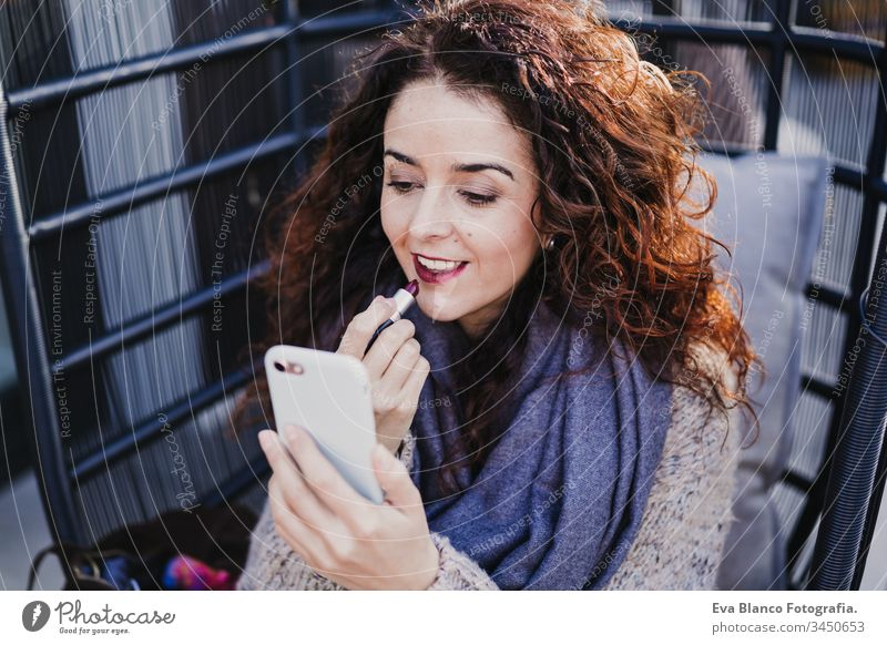 portrait of young beautiful woman using red lipstick outdoors in a terrace. Using mobile phone as mirror. Make up and lifestyle concept make up smiling