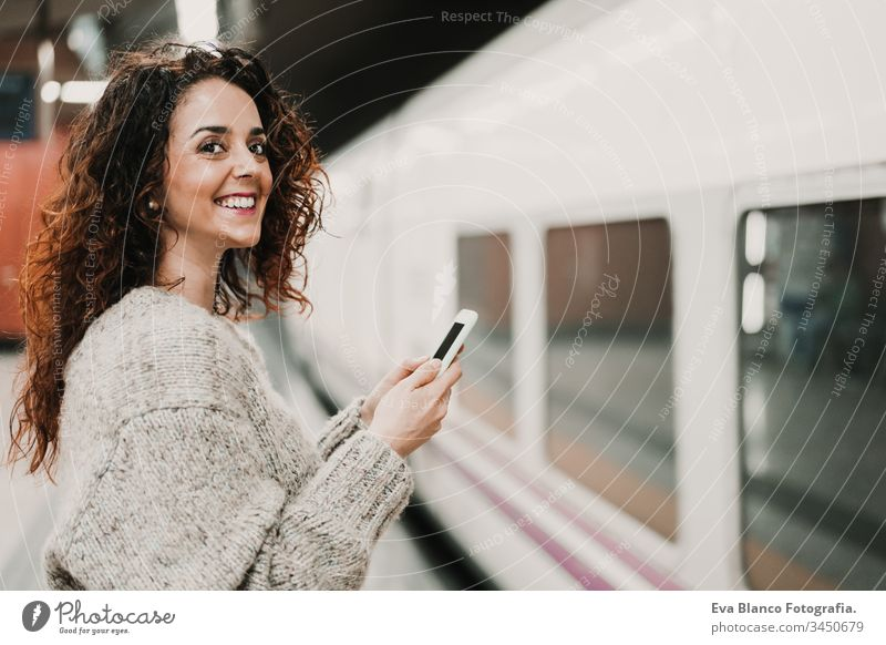 young beautiful woman at train station using mobile phone before catching a train. Travel, technology and lifestyle concept travel moving caucasian madrid