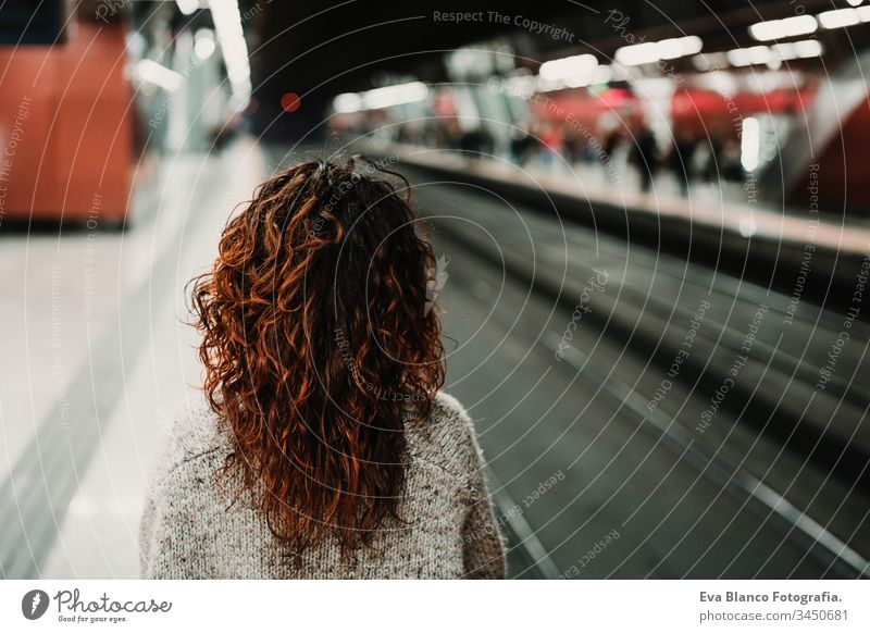 young beautiful woman at train station using mobile phone before catching a train. Back view. Travel, technology and lifestyle concept travel moving caucasian