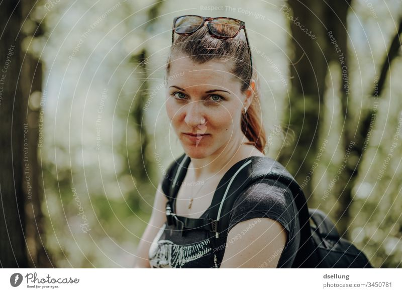 Young woman hiking in the forest with a view into the camera. So of course she does not go hiking with her gaze into the camera, but with her husband, who takes pictures of her looking into the camera.