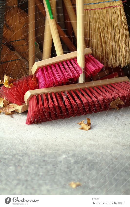 Broom with red bristles and sweeper with straw bristles, stand after work done, tidy in the garage, summer house, broom closet. Work and employment Cleaning