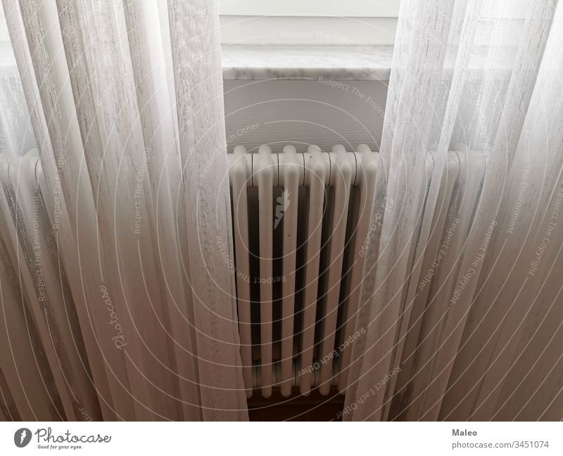 The central heating radiator is covered with light white curtains house room interior background window bland airy architectural architecture bright building