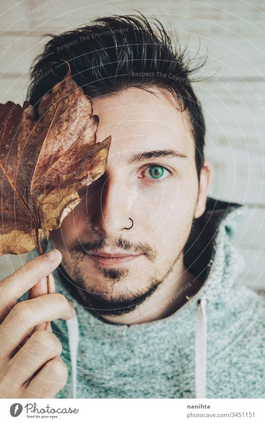 Young man covering his face with a dry leaf attractive cool male portrait autumn creative artistic beard piercing nose close handsome guy young youth lenses