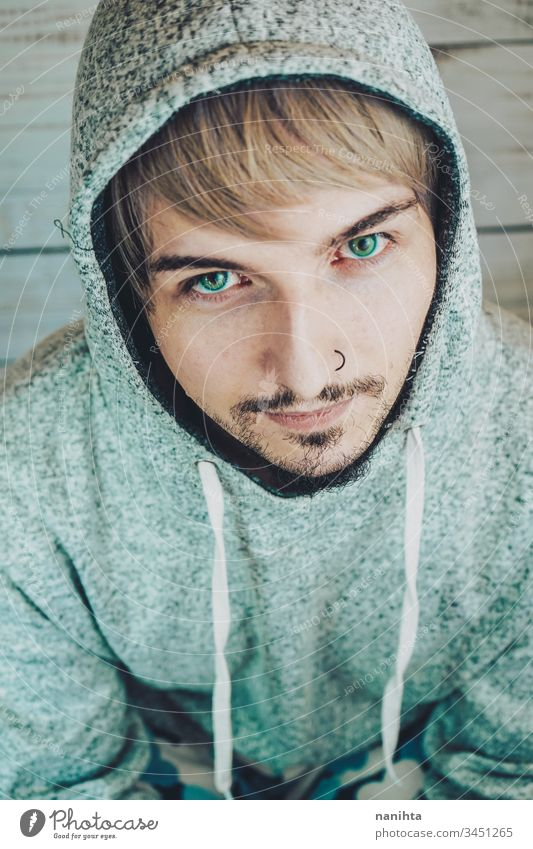 Portrait of an attractive male in his home handsome man sad isolated nostalgia romantic alone lonely hairstyle casual trendy sport hood hoodie beard bearded