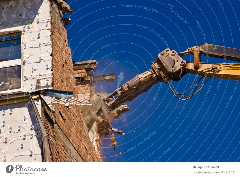 Demolition of a building with a crane against a blue sky Profession City Building owners Old House (Residential Structure) aborting Crush Exterior Architecture