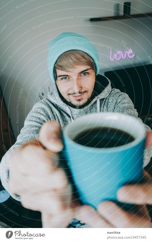 Young man enjoying a cup of coffee at home male cozy isolated quarantine blue attractive handsome guy casual wear pajama tea black tea drink drinking hot drink