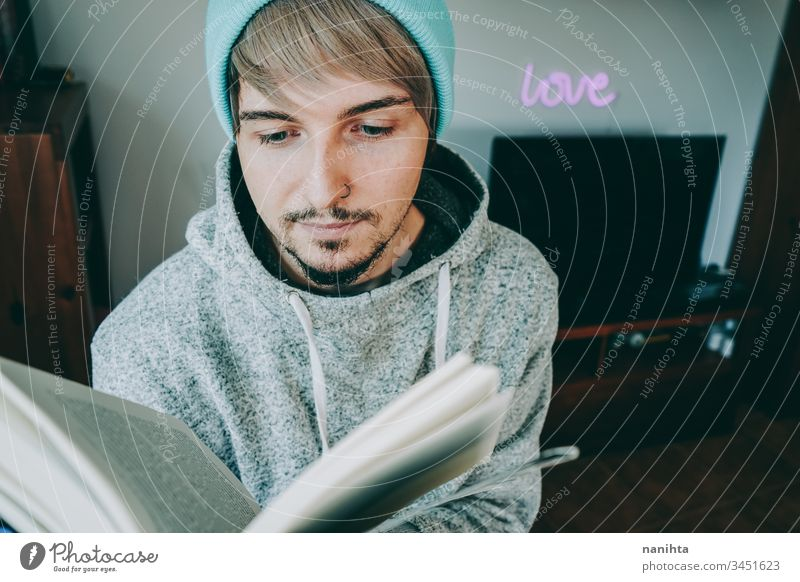 Young man reading a book in his home attractive quarantine hobby leisure relax enjoying learn study student young youth indoors room decoration life casual real