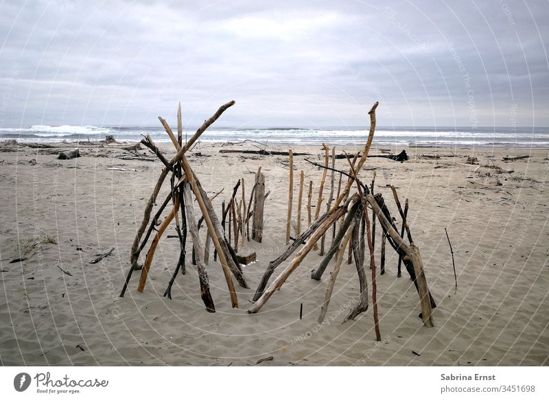 Wooden tent on a beach in Oregon wooden Tent Beach Sand Ocean Water Gray inclement weather travel Beautiful vacation Rough Waves Sticks homemade