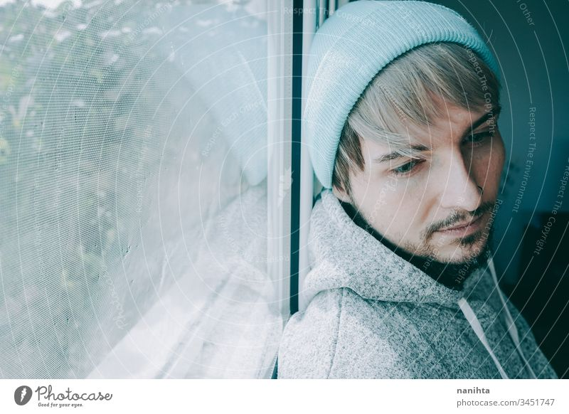 Young man alone in his home near a window male portrait isolated locked quarantine lonely self attractive handsome guy casual wear hairstyle blue eyes lenses