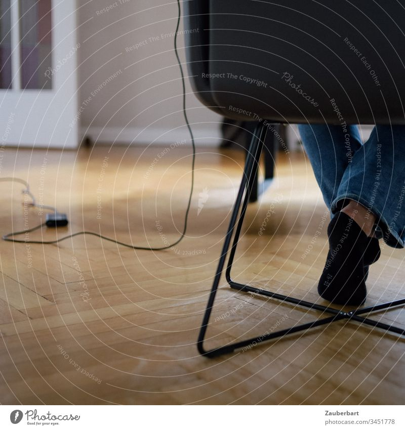 Legs of a woman sitting on a chair in her home office, with cable and power supply of her computer, on parquet floor Chair Sit feet socks Cable Power cord