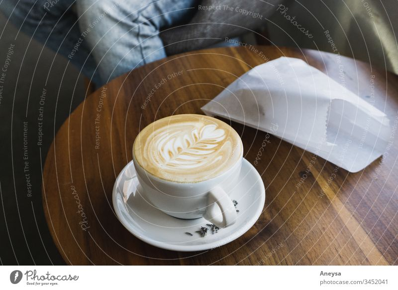 A latte and pastry on a table 2017-2020 first import latte art coffee coffee shop coffee cup Coffee break meeting date bistro pastry bag Latte macchiato Cup