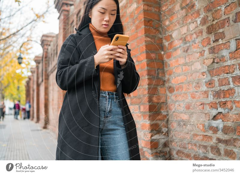 Asian woman using her mobile phone. street smartphone asian people urban cellphone female text young sms message outdoor adult online internet use japanse