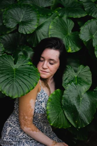 A young woman surrounded by leaves 2017-2020 first import elephant ear elephant ear plant garden Young woman Weather tropical plant Floral Foliage plant foliage