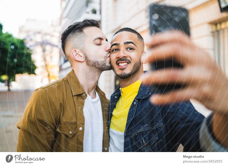 Gay couple taking a selfie in the street. gay love relationship mobile phone date lovely partnership positive city freedom life young pride dating looking