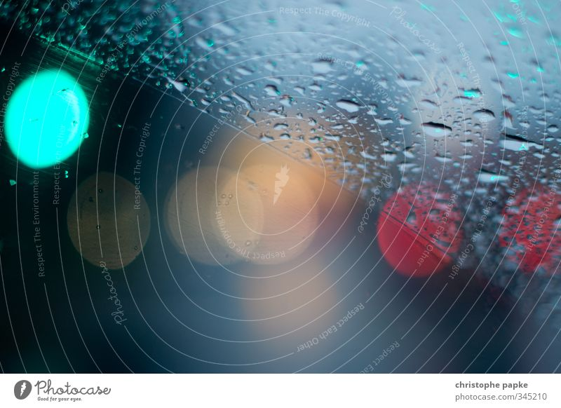 two-part Bad weather Rain Transport Car Water Wet Weather Divided Drops of water Windscreen Windscreen wiper Traffic light Point of light Colour photo Close-up