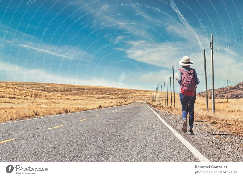 Beautiful woman hitchhiking on road in forest, hitchhiking with thumbs up in a countryside road, Travelling and hitchhiking concept. outdoors suitcase walking