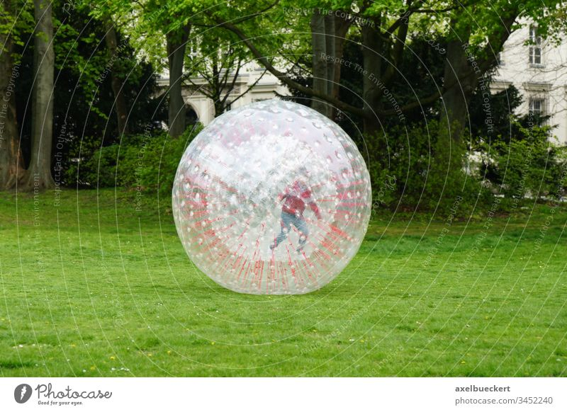 unrecognizable kid zorbing in park play playing rolling childhood plastic recreation outside globe-riding sphereing bubble fun ball sport joy activity leisure
