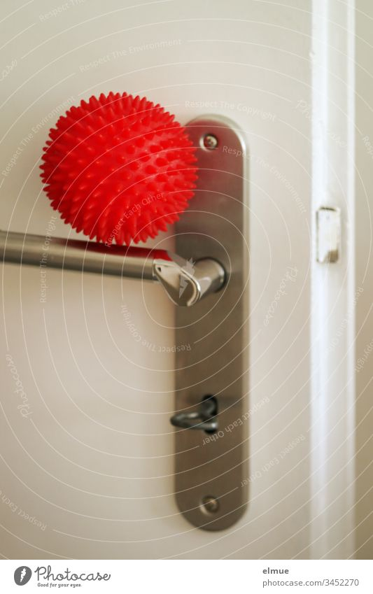 red ball as a symbol for corona virus lies on a door handle coronavirus covid-19 Infection risk of contagion lubricant infection transfer Virus flu Illness Clue