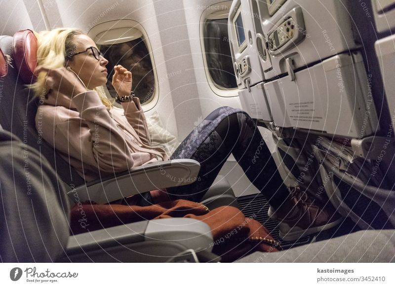 Sporty casual young blonde caucasian lady watching movie while traveling by airplane by the window. Commercial transportation by planes flight entertainment