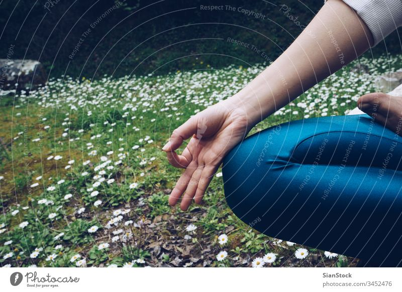 Young woman is sitting in lotus pose, outdoors in spring time with daisies yoga young nature meditation daisy healthy background exercise green grasses position