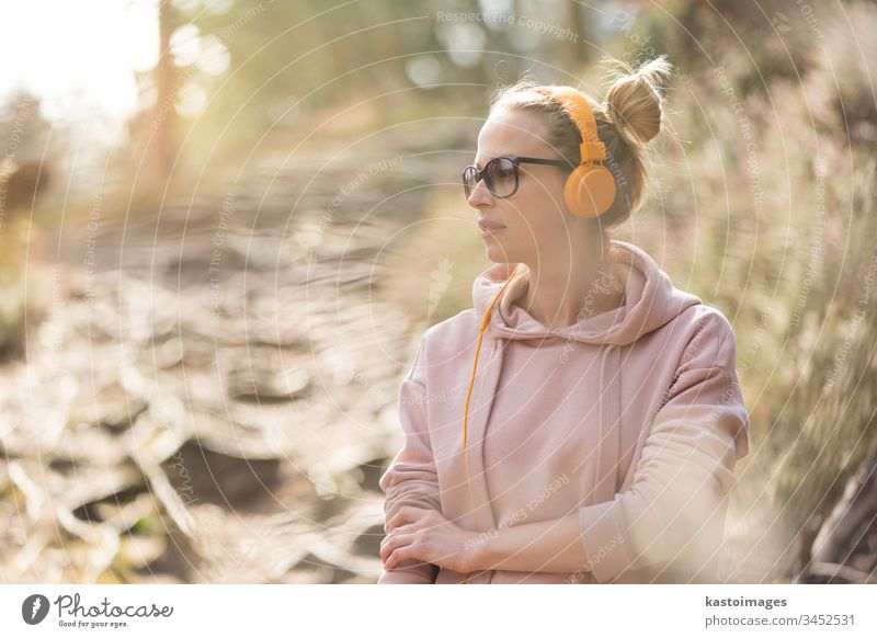 Portrait of beautiful sports woman wearing sunglasses, hoodie and headphones during outdoors training session girl portrait nature workout active runner