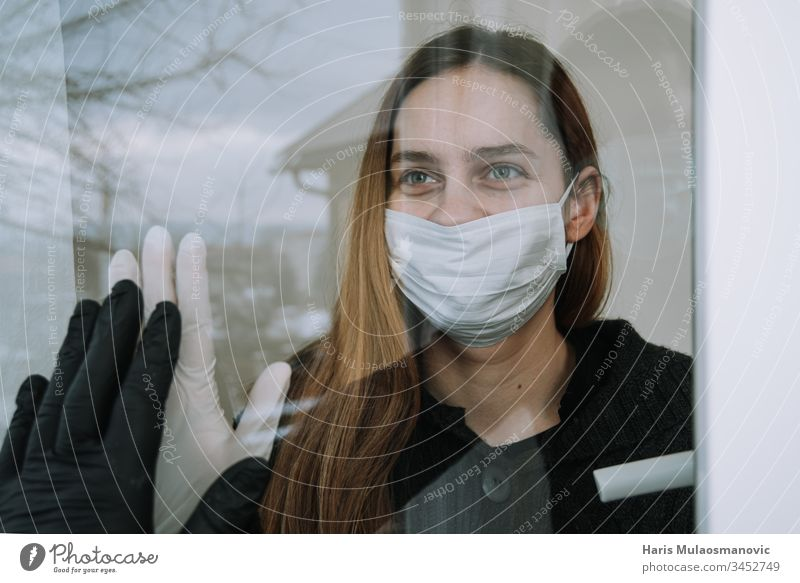 happy woman seeing her fried who came to visit her due to coronavirus covid-19 wit mask and gloves on window at home social distancing adult cage china concept