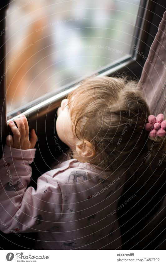 little girl looking out the window baby blonde caucasian concept coronavirus covid.19 flu home house kid outdoor person portrait quarantine stay stay at home