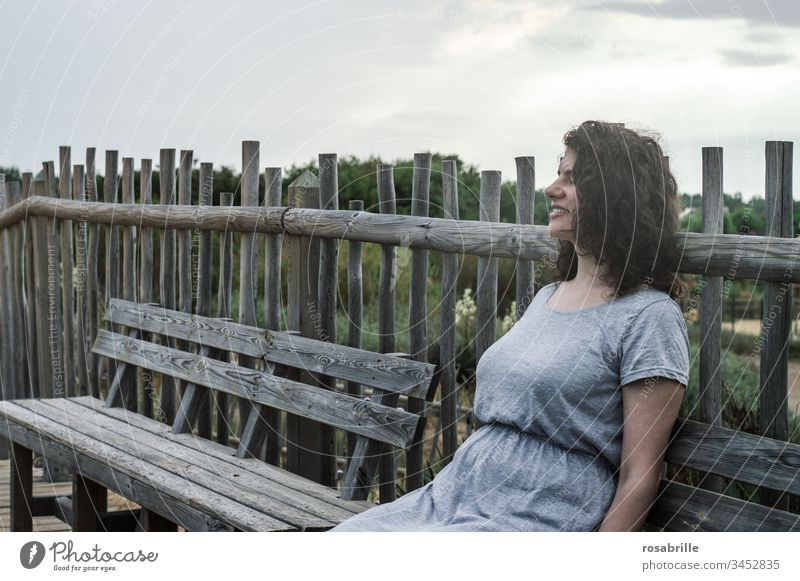 young pretty brunette woman with curly hair sits on a wooden bench in front of a board fence in the dunes near the beach and enjoys the holiday youthful