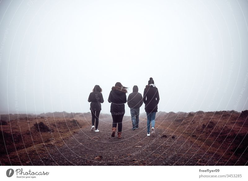 Four people hiking with fog active background cold copyspace foggy landscape four friends friendship fun group happy lifestyle mist outdoor sky summer top