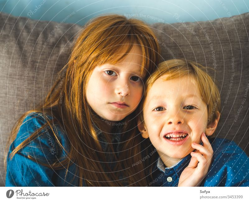 Two blonde little kids in blue shirts on sofa child smile face hug family love siblings brother sister redhead funny sweet tender together near indoors portrait