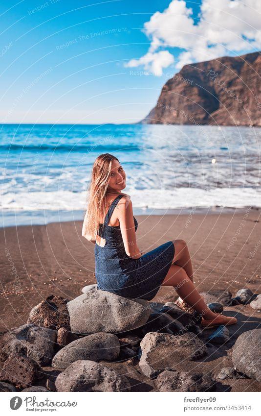 Young woman in Los Gigantes beach in Tenerife, Canary Islands, Spain alone atlantic background backward beauty blond blue canary island cliff coast coastal