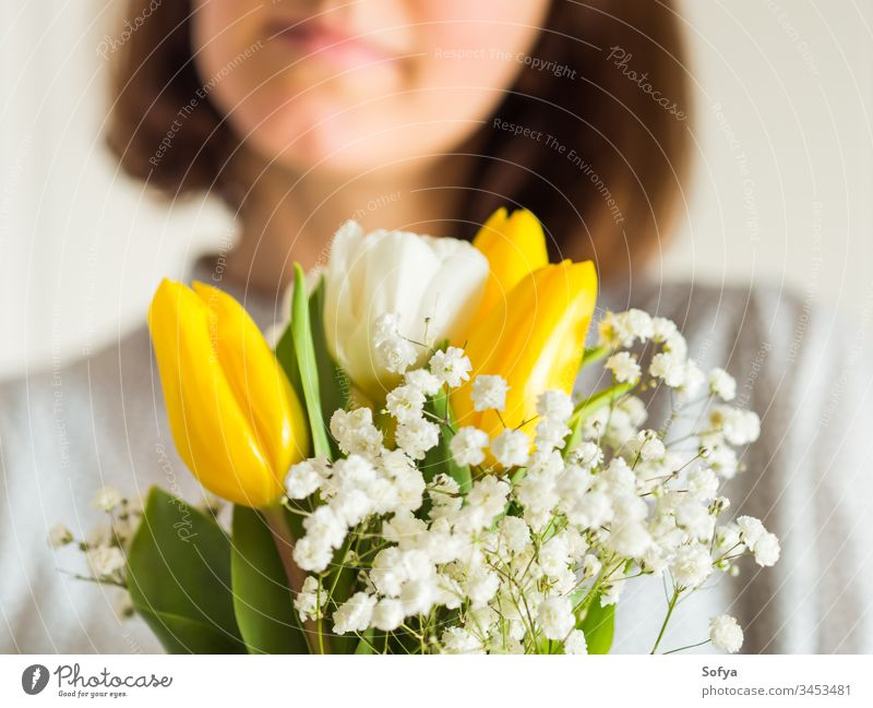 Woman holding bouquet of tulips. Woman's day flower bunch mother woman give spring easter hands floral white yellow lady march gift invitation greeting card