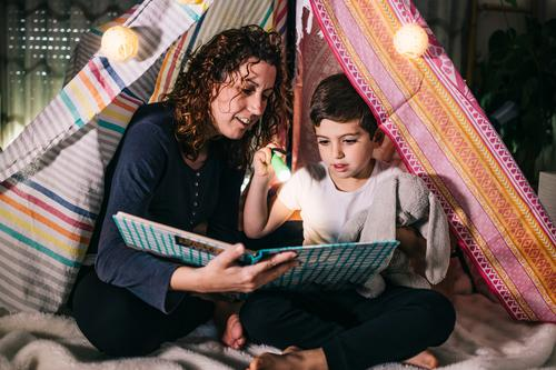Mother and son reading a book on a tent at home beautiful bedroom bedtime caucasian child childhood concept cute dark daughter day education family female