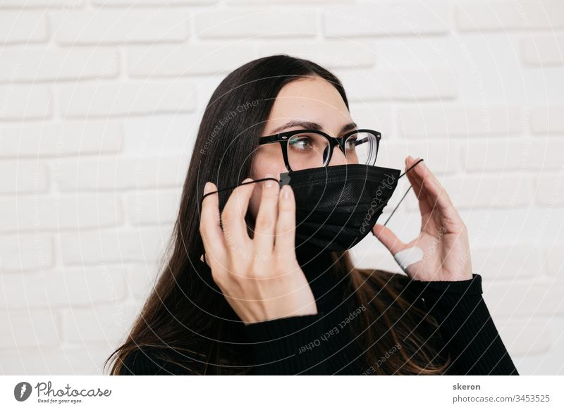 brunette girl in glasses for vision correction is protected from a viral infection: coronavirus. A woman in a black medical mask during the pandemic  2019-nCoV COVID. the patient in quarantine
