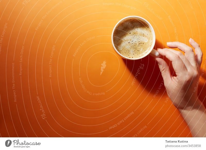 A cup of black coffee with a female hand on a bright orange background. Minimalism, top view. copyspace mug drink design cafe food hot breakfast paper white