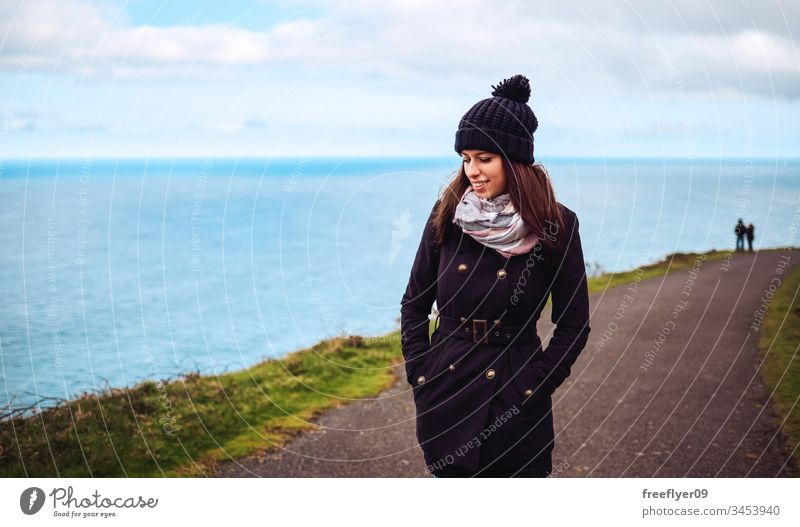 Portrait of a young woman in winter walking by the sea adventure attractive autumn away back background beautiful beauty behind black clothes cold concept day