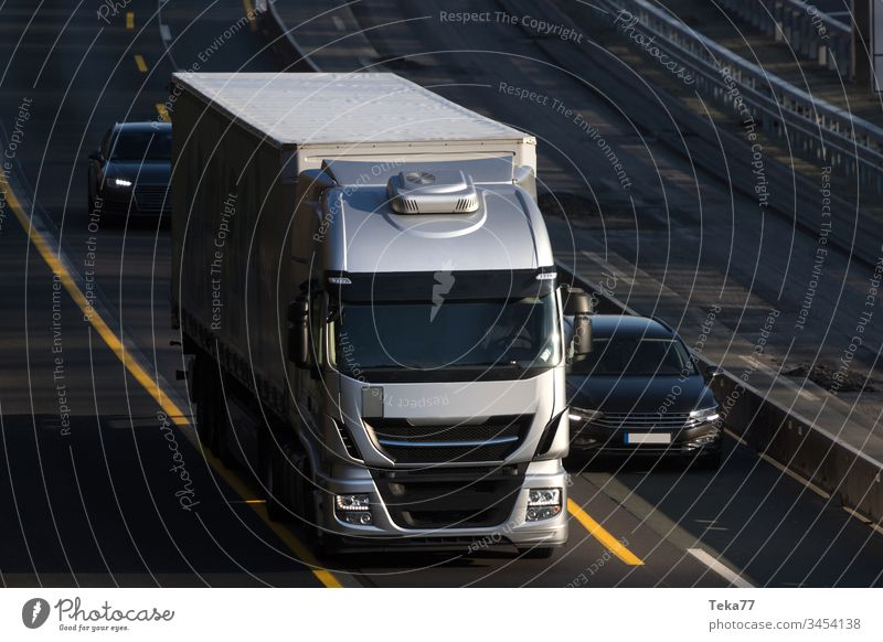 a modern grey truck driving on an highway car cargo cargo truck city close up clouds globalisation light lights plain street streets traffic transportation
