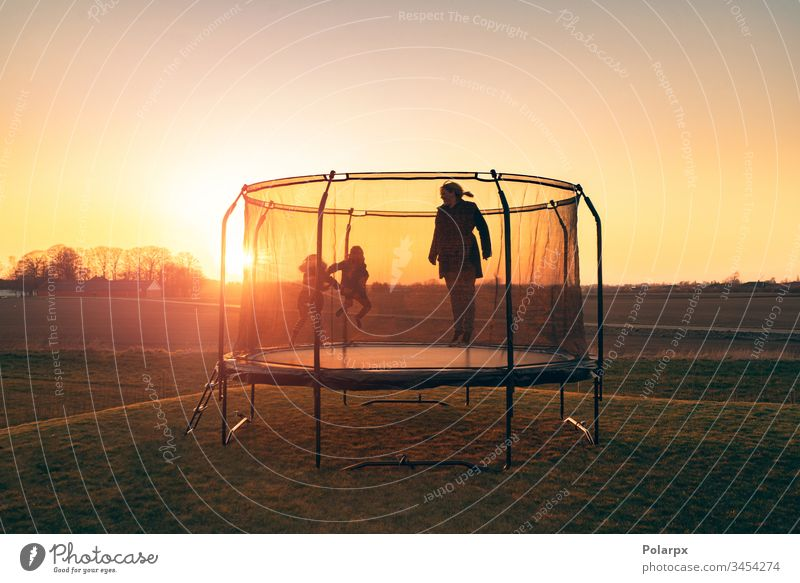 Trampoline on a lawn in the sunset with two kids recreation silhouettes dawn sunrays blond children balance action gymnastics sport garden positive girl