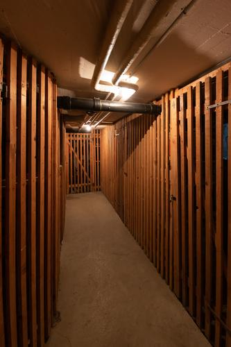 Underground communal cellar corridor artificial illumination wooden dividing doors house empty housing unit neglected darkness storage decay deep wooden door