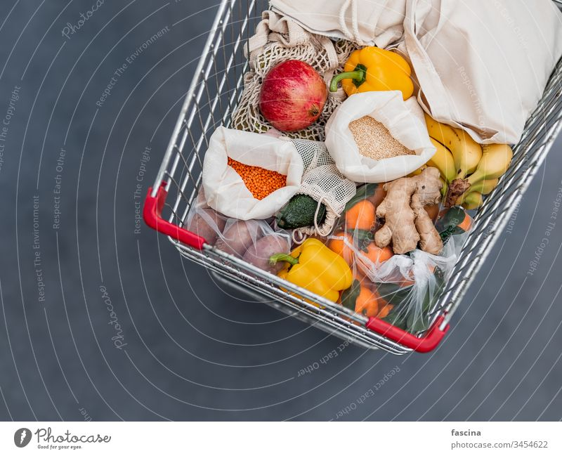 Food waste, zero waste shopping in supermarket eco bag shopping cart food waste trolley fruit vegetables reusable bags grains textile fabric pouch top view flat
