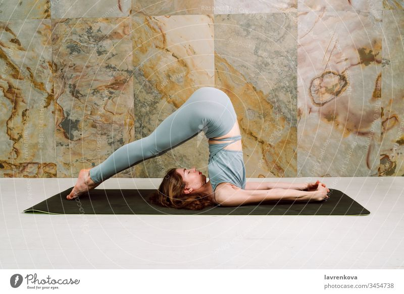 Young yogini practicing Halasana (plow pose) in pastel blue leggins and top, selective focus active athlete athletic attractive body brunette calm caucasian