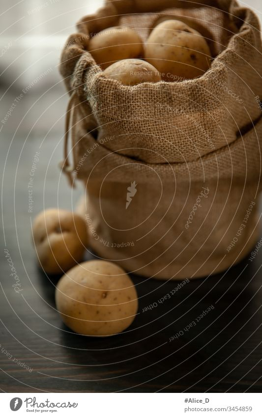 Potatoes in burlap on a rustic wooden background Bag Brown sackcloth burlap sack Close-up Culinary Diet Earth Earthy plummeting Food Fresh fresh potatoes Group