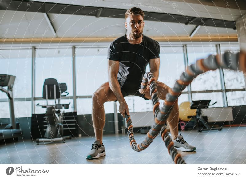 Young man practicing with battle ropes in the gym muscular strength fitness workout healthy sport male strong young exercise body muscle power athlete active