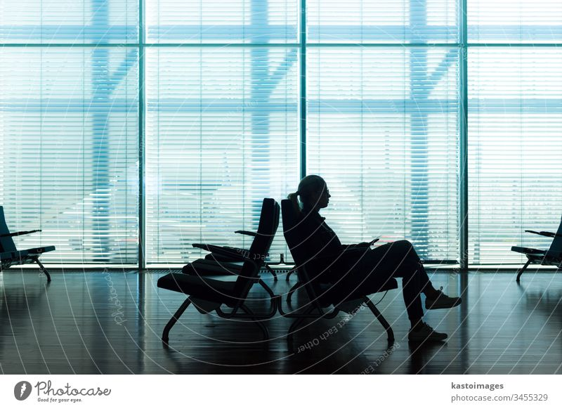 Woman in transit waiting on airport gate. waiting room waiting area lobby business passenger office hall window glass blinds time travel silhouette