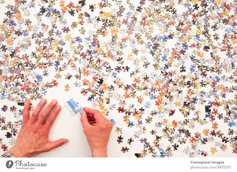 Personal perspective of a man doing a jigsaw puzzle abstract brain-teaser brainteaser challenge concept connect connection creative creativity educational