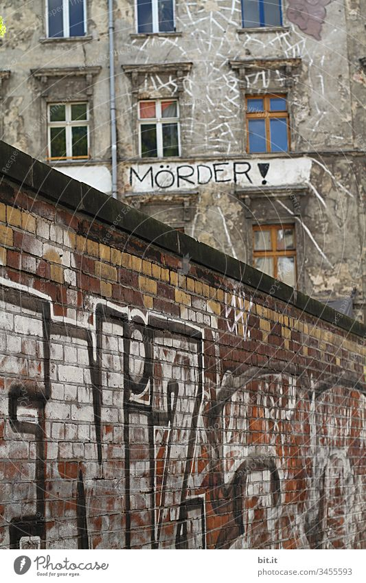 Murderer, standing in black letters, as lettering, on an old squat house, with many windows, behind a brick wall painted with graffiti. Sign as an appeal against racism, war, hatred, violence, brutality and discrimination.
